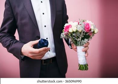 Groom holds wedding bouquet and velvet gift box