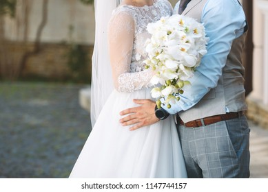 groom hugging bride with white orchid bouquet