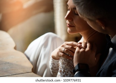 Groom hugging his bride in sitting at the wooden table on outdoor
