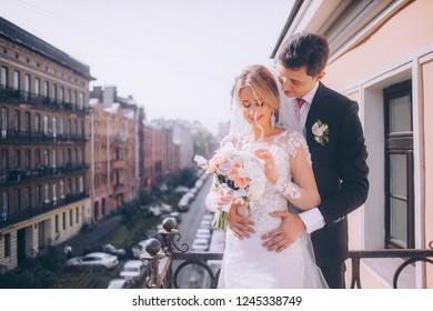 Groom hugs bride on hotel balcony on wedding day overlooking big city
