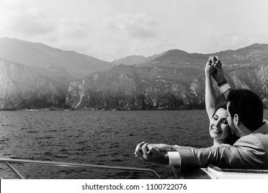 Groom hugs bride tender from behind while they enjoy the wind over the lake before mountains