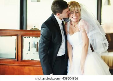 Groom hugs bride's shoulders while she laughs