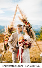 The groom hugs his bride standing under the arch outdoors. Wedding in rustic style