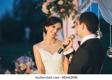 花婿はマイクを持ち、花嫁に向かって話す