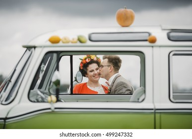groom kisses bride near the car