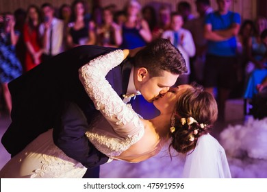 Groom kisses bride while bending over during their first dance