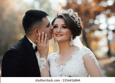 The groom kisses the cheek of the bride. Stylish and beautiful. The groom in a black suit. Happy and young married couple. Autumn wedding