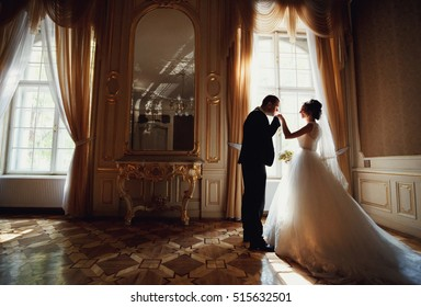 Groom kisses a hand of a bride in the luxury room