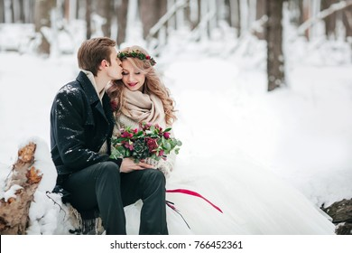 Groom küsst seine Braut auf dem Tempel auf dem Hintergrund des schneebedeckten Waldes. Winterhochzeit. Kunstwerke. Leerzeichen kopieren