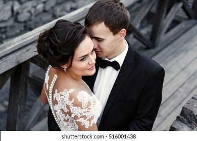 Groom leans to stunning bride outside