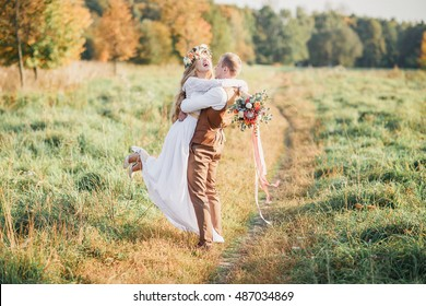 The groom lifted the bride up in his arms. The bride in the arms of the groom laughing.