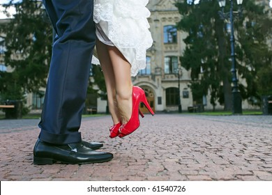 Groom lifting his bride up during their walk, close-up of lower part of the bodies