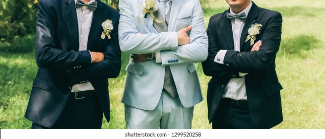 Groom in light blue suit is standing with best man friends. Elegant photo. Outdoors wedding walk. Sunny day.