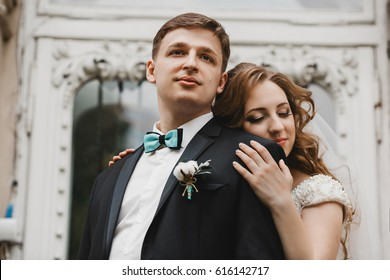 Groom looks far away while bride lies on his shoulder