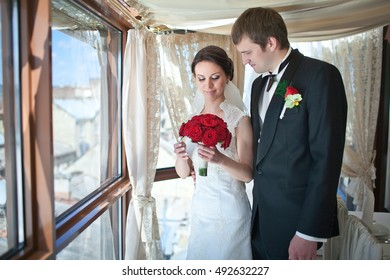 Groom looks at pretty bride with red rose bouquet in her hands