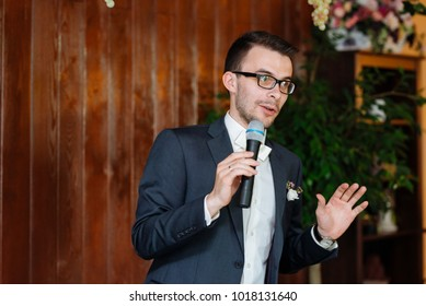 The groom with the microphone says a toast. Businessman at a conference