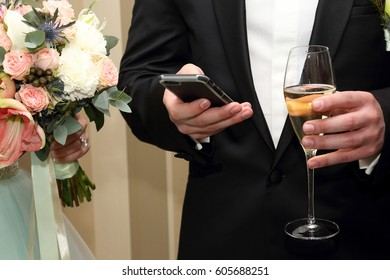 the groom with mobile and glass in hand