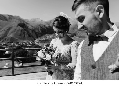 Groom in modern suit and bride in charming pink dress pose on the terasse with great mountain view in Georgia