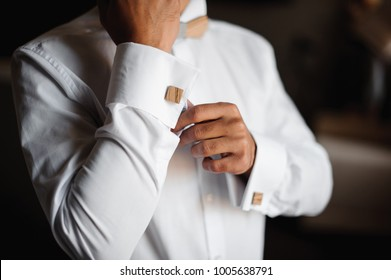Groom morning preparation. Young groom getting dressed in a wedding shirt with wooden bow tie and cufflinks