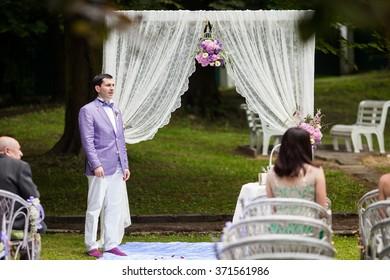 Groom near beautiful white wedding aisle archway with purple flowers