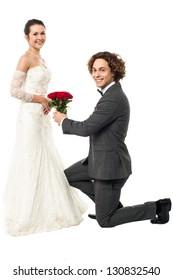 Groom on his knees making love, wedding proposal.