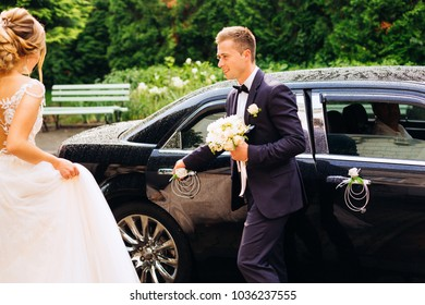 the groom opens before bride door to a chic black car