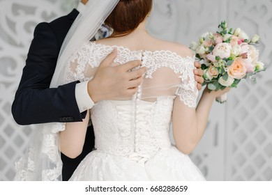 Groom passionately hugs beautiful bride with white veil the back view