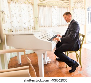 groom playing on a piano in the room