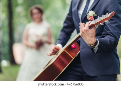 The groom plays the guitar for the bride during wedding ceremony