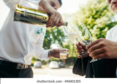 Groom pouring golden champagne in glasses at wedding ceremony