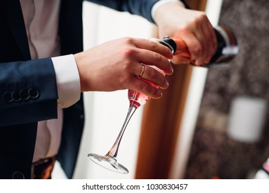 groom pours red champagne from a bottle into a close-up glass