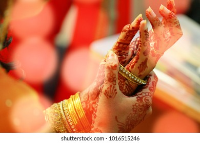 groom puts bangle in bride hand at bangle ceremony with lights.