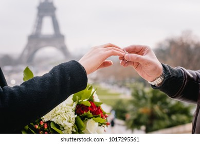 Groom puts engagement ring on a brides hands under the Eiffel Tower in Paris, France.