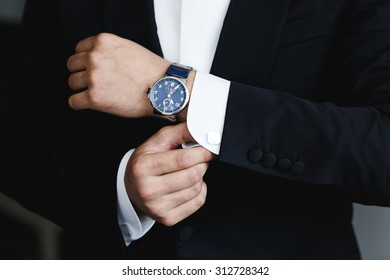 the groom puts on a watch