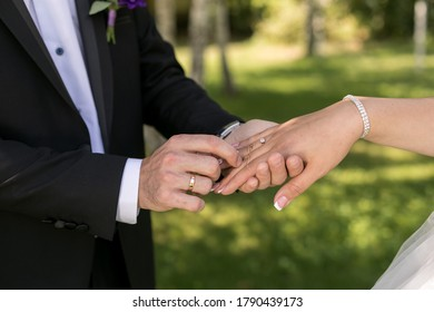 the groom puts on the wedding ring to the bride