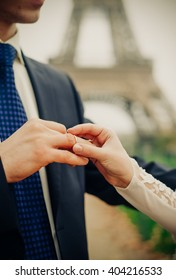 Groom puts ring on a brides hands under the Eiffel Tower in Paris, France.