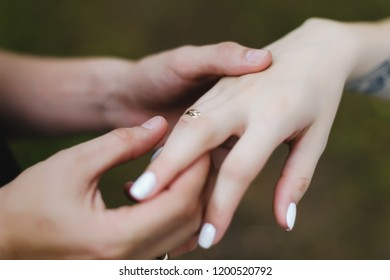 Groom puts the ring on the finger of the bride. Hands of groom and bride with rings.  wedding details