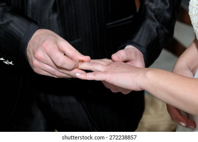 groom puts the ring on the finger of the bride during the wedding