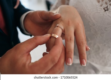 The groom puts the ring on the future wife. Hands with wedding rings