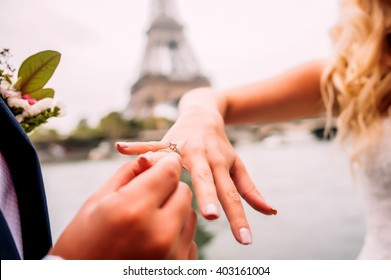 Groom puts a wedding ring on a brides hand under the Eiffel Tower