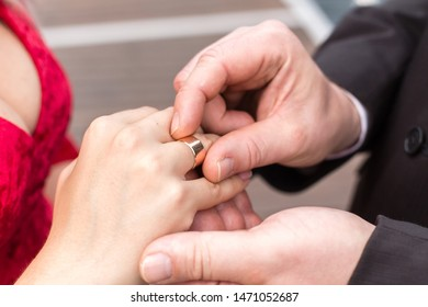 Groom puts a wide wedding ring on the finger of Bride, dressed in a sexy red dress with a decollete.