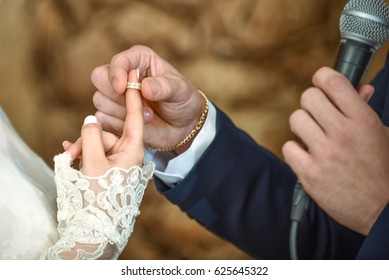 Groom putting golden ring on bride's finger during jewish wedding ceremony