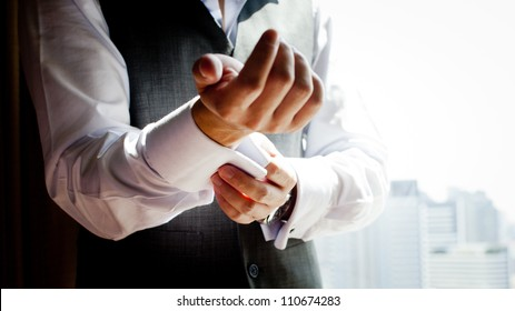 A groom putting on cuff-links as he gets dressed in formal wear .Groom's suit