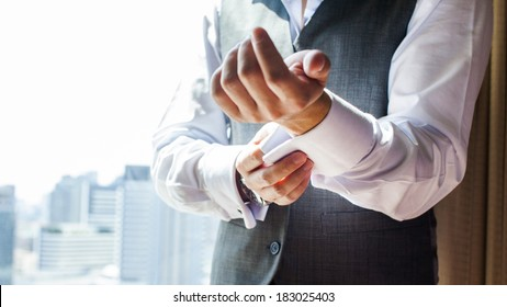 A groom putting on cuff-links as he gets dressed in formal wear