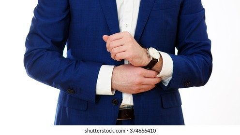 groom putting on cufflinks as he gets dressed in formal wear close up, of a hand how wears white shirt, business photo