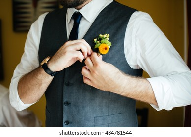 Groom putting on his boutonniere