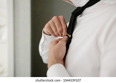 bc419505e820 Groom Putting Silver Tie Clip on His Black Tie and White Dress Shirt