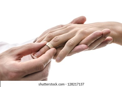 Groom putting a wedding ring on the finger of the bride. Isolated over white background.