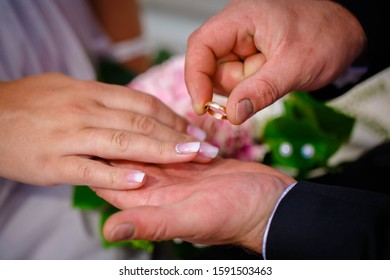 Groom putting wedding ring on bride's finger during the wedding ceremony
