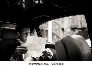 Groom reads his wedding speech sitting on the back seat in the car